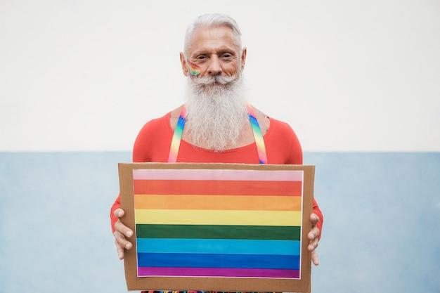 レインボーlgbtバナーを保持しているゲイプライドの流行に敏感な年配の男性-顔に焦点を当てる