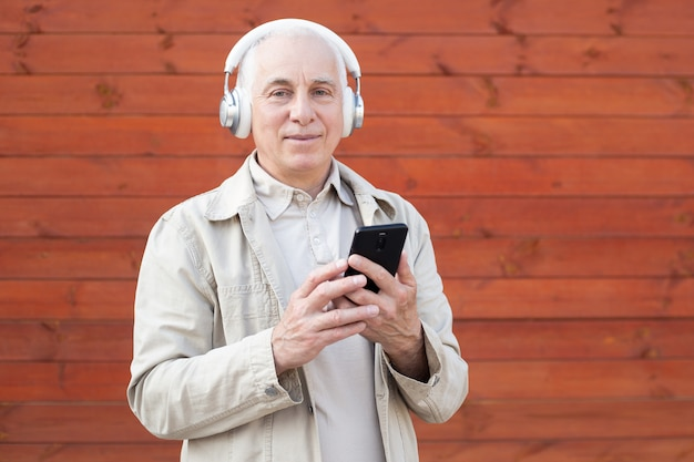 Hipster senior man having fun using mobile smartphone playlist apps. happiness, technology and elderly lifestyle people concept