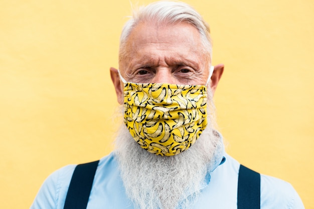 Hipster senior man wearing trendy face mask during coronavirus outbreak - old fashion and washable eco cotton concept - focus on mask