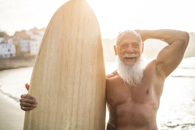 Hipster senior surfer holding vintage surf board on the beach in summer sunset - focus on face