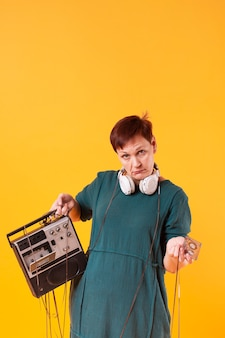 Hipster senior woman holding retro cassette player