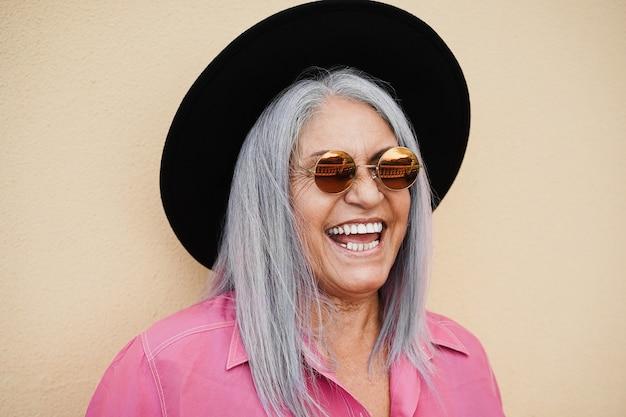 Хипстерская старшая женщина в солнцезащитных очках на открытом воздухе с желтой стеной - фокус на лице