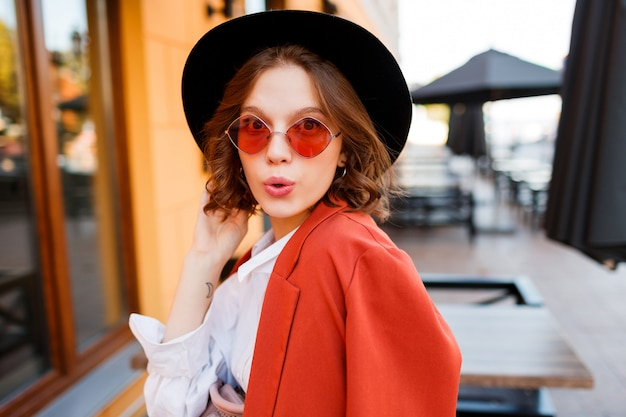 流行に敏感な短い髪の女の子が既存の顔でウインクしています。スタイリッシュな表情。オレンジ色のジャケットと黒い帽子。