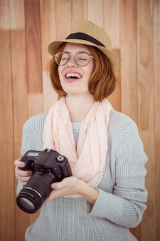 Hipster smiling and holding camera