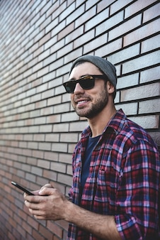 レンガの壁の背景の街の通りに流行に敏感なsmsテキストメッセージ電話アプリ。スマートカジュアルウェアでスマートフォンを持って立っている素晴らしい男。都会の若いプロのライフスタイル。