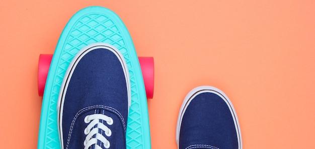 Хипстерские кроссовки на скейтборде сверху на коралловом фоне. концепция моды минимализм