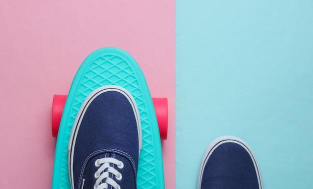 ピンクブルーのパステルカラーの背景にスケートボードの上面図の流行に敏感なスニーカー。ミニマリズムのファッションコンセプト