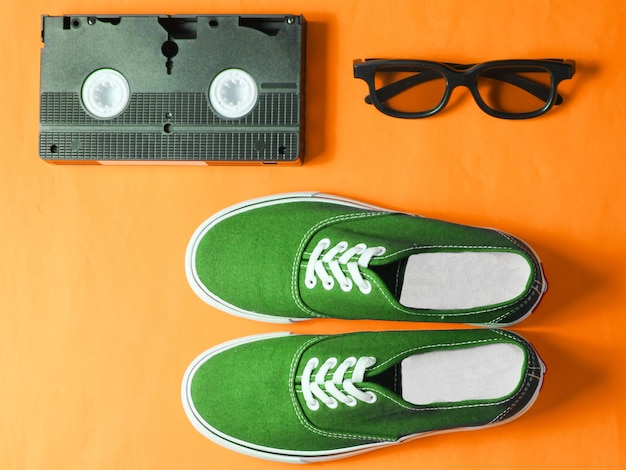 Hipster sneakers, vinyl plate, audio and video cassette, 3d glasses