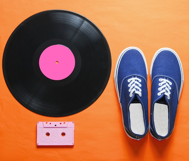 Hipster sneakers, vinyl plate, audio and video cassette