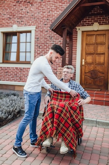 Hipster son walking with disabled father in wheelchair at park