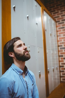 Hipster student feeling sad in hallway