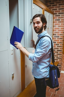 Hipster student smiling at camera in hallway