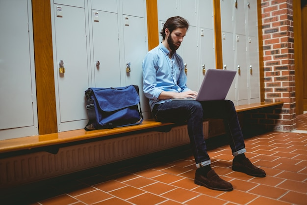 Hipster student using laptop in hallway