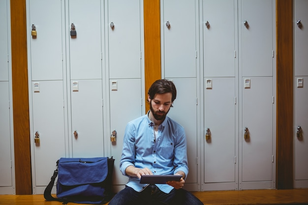 Hipster student using tablet in hallway