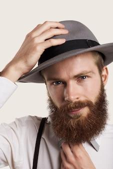 Ritratto maschile barbuto stile hipster in grande cappello grigio e camicia bianca