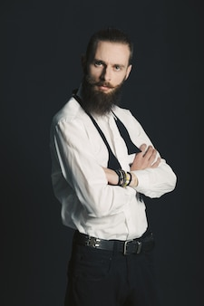 Hipster style bearded man white shirt in studio over black background