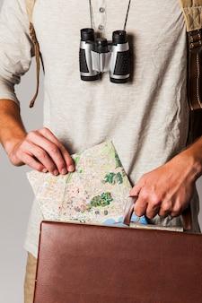 Turista in stile hipster con mappa e valigia