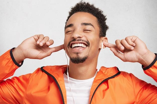 アフリカの髪型を持つ流行に敏感なスタイリッシュな男は喜びで目を閉じ、楽しさと幸せを感じ、