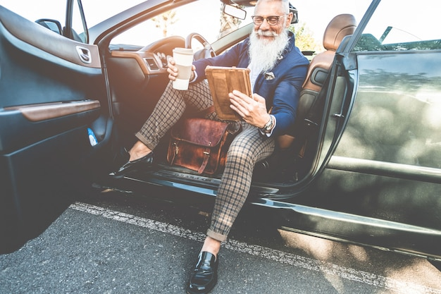 Hipster stylish man using tablet sitting inside convertible electric car - senior entrepreneur having fun with technology trends - tech, ecologic systems and fashion concept - focus on face