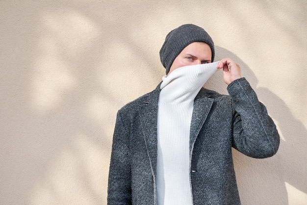 Hipster stylish man wearing a fashionable gray coat hiding face with white sweater.