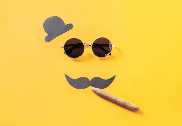 Hipster sunglasses and funny moustache with hat and cigar on yellow