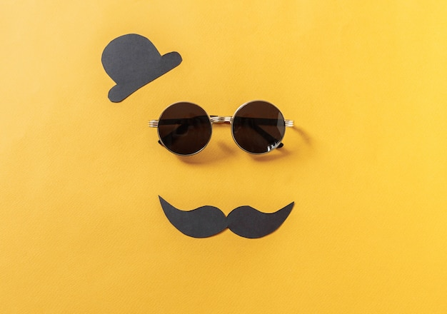 Hipster sunglasses and funny moustache with hat on yellow
