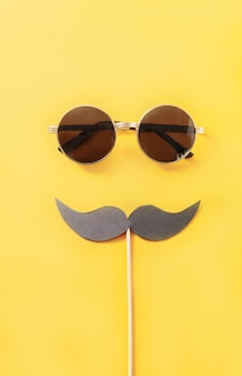 Hipster sunglasses and funny moustache on yellow