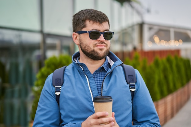 Hipster in sunglasses is drinking coffee from paper cup on city street.
