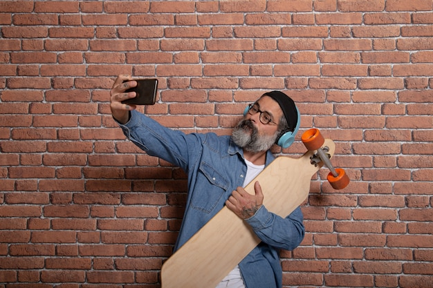 A hipster takes a selfie on his smartphone with the longboard on a brick wall.