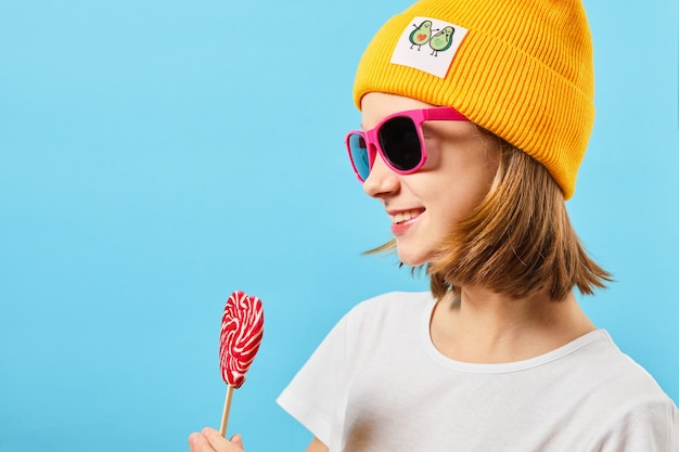 Hipster teen girl in trendy glasses wearing knitted hat and holding lollipop. pretty fashionable woman with a candy near the face.