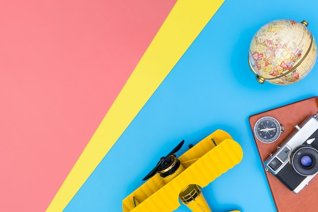 Hipster travel blogger writer accessories flatlay on blue yellow and pink