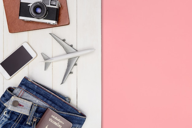 Hipster travel blogger writer accessories flatlay on white wood with pink copy space