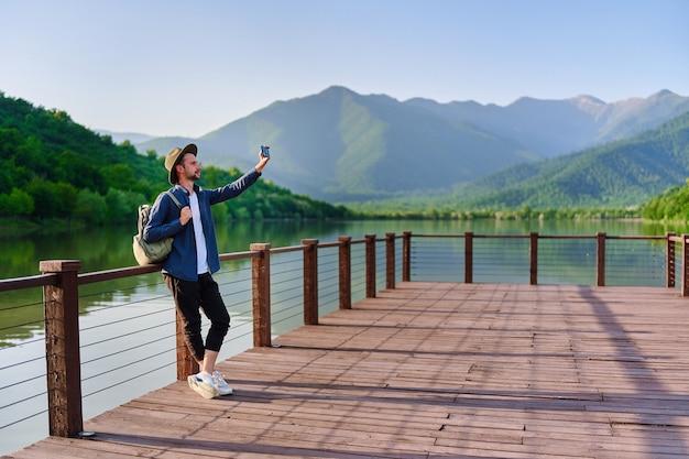 湖と山の景色を望む桟橋に一人で立っている流行に敏感な旅行者のバックパッカー。自然の中で美しい自由の瞬間の生活と穏やかで静かな平和な雰囲気を楽しんでいます。コピースペース
