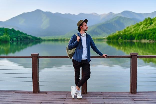 湖と山の景色を望む桟橋に一人で立っている流行に敏感な旅行者のバックパッカー。自然の中で美しい自由の瞬間の生活と穏やかで静かな平和な雰囲気を楽しむ