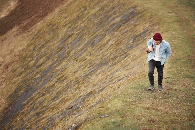 自然の中を歩くカジュアルな服装の流行に敏感な旅行者は、丘を登り、男は自信を持って歩きます。