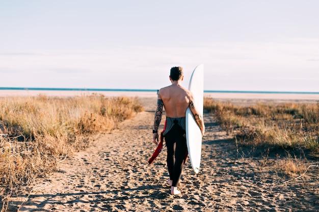 Surfista alla moda hipster sulla spiaggia con tavola da surf