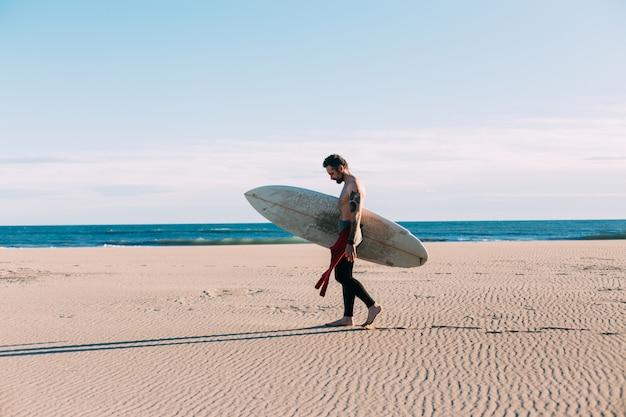 サーフボードとビーチで流行に敏感なトレンディなサーファー
