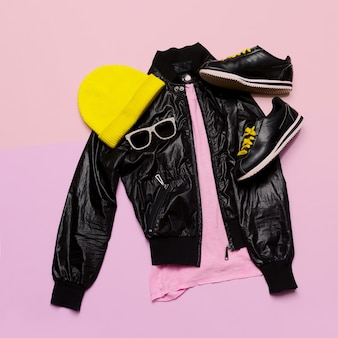 Hipster urban outfit girl stylish black clothes and bright accessories sneakers hat sunglasses