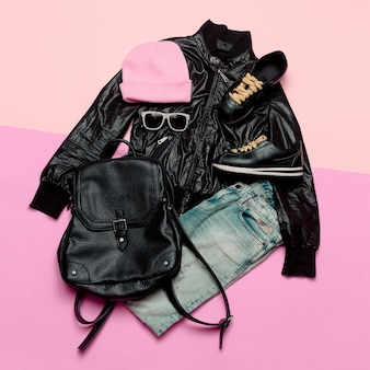 Hipster urban outfit girl stylish black clothes and bright accessories stylish backpack and beanie
