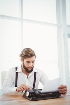 Hipster using typewriter at desk in office