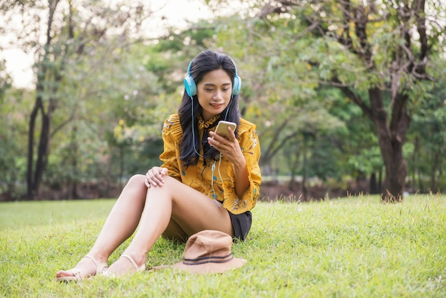 Hipster in vintage costume play smartphone in park