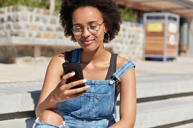 Hipster with dark skin, crisp hair, recieves text message on cell phone, wears denim dungarees, optical glasses, round earrings, watches video in internet, relaxes outdoor, makes online shopping