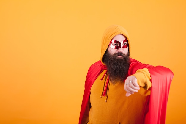 Hipster with long beard dressed in superhero costume looking away over yellow background. yellow hoodie. red mask. brave man.