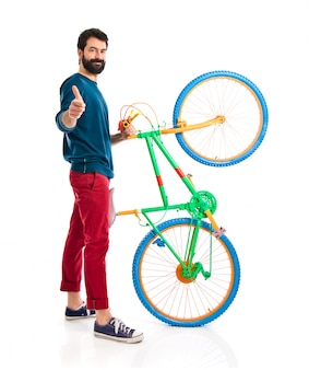 Hipster with thumb up holding a bike