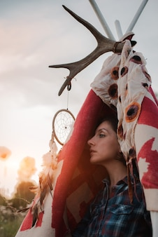Hipster woman in the form of a shaman is looking for inspiration from mother earth in a wigwam in nature.
