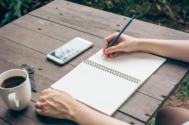 Хипстер женщина рука, писать ноутбук бумаги в кафе.