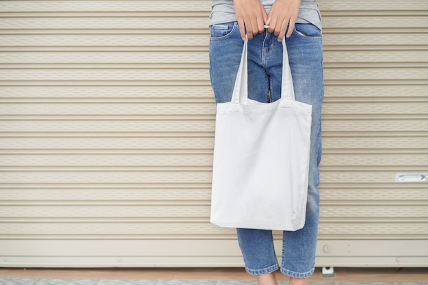 Hipster woman holding white tote bag