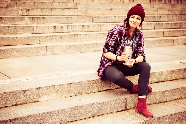 Битник женщина в повседневной одежде сидит на ступеньках в городе