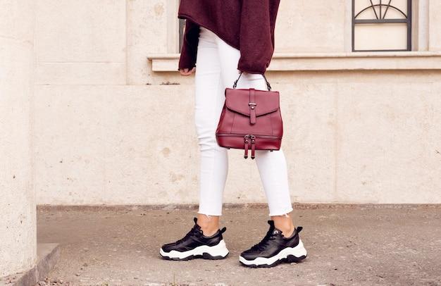 베이지 색 벽 근처 빨간 가방 패션 블랙 스 니 커 즈에서 hipster 여자.