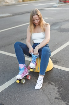 Hipster woman putting on inline skates outdoors close up sport lifestyle